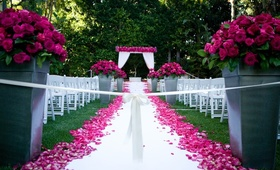 Wedding ceremony on grass lawn with hot pink flowers