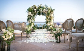 Beautiful ceremony with ocean view white flower petals aisle runner lanterns white roses greenery