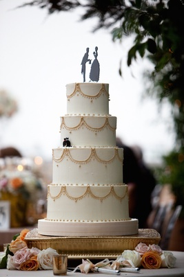 Simple white cake with gold piping and whimsical topper