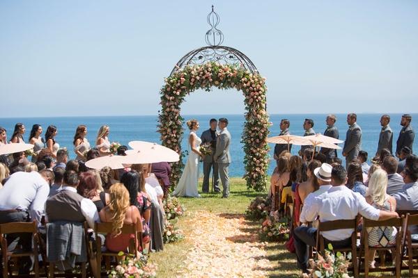 Bride in Ines Di Santo wedding dress under ceremony arch guests with parasols sunny summer wedding