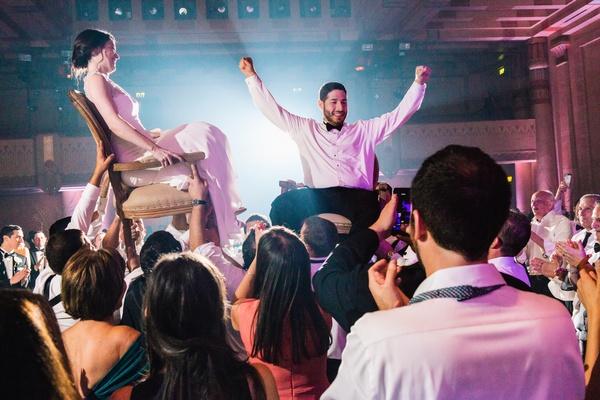 newlyweds lifted up during the horah at jewish wedding reception in Atlanta