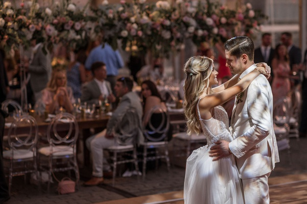 wedding reception first dance bride in boho wedding dress groom in ivory suit guests at head tabl