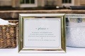 White sign with green type in silver frame instructing guests to not take photos during the ceremony