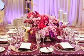 pink and purple floral arrangements centerpieces purple linens glass plateware reception