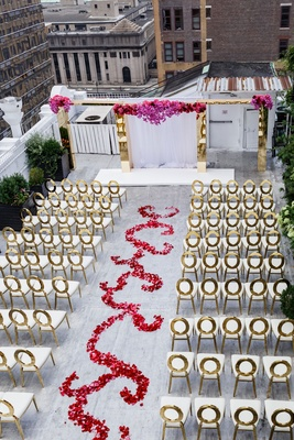 Aerial view of rooftop wedding ceremony gold chairs flower swirl aisle gold archway altar white