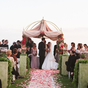 pink and red roses petals cover aisle leading to chuppah