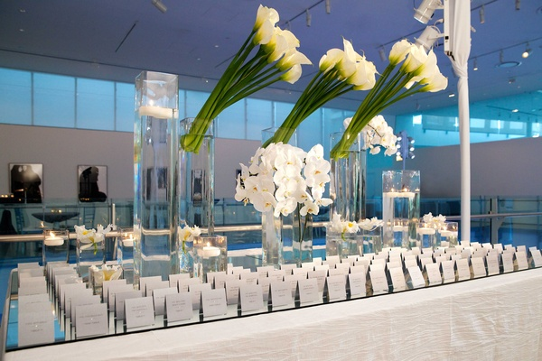 Mirror table with escort cards and white orchids and calla lilies