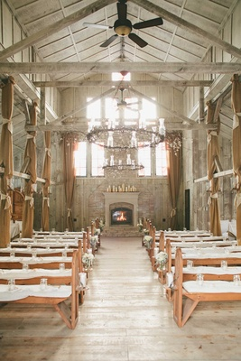 Wedding ceremony with benches white cushions fireplace medieval chandeliers wood beams ceiling fans