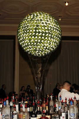 Globe of green limes and white flowers on glass vase