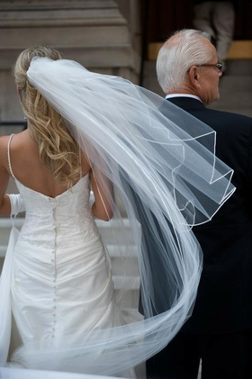 Bride in veil and spaghetti strap dress with embroidered bodice with father outside the church