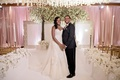 bride and groom on white ceremony aisle orchid tall taper candles gold chairs circle flower