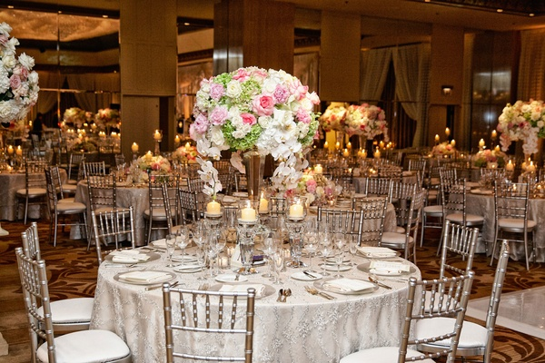 Wedding reception table with rose, hydrangea, orchid in white, pink, and pale green in crystal vase