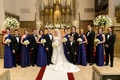 Bride and groom at church with blue bridesmaids and tux groomsmen