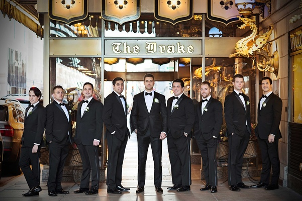 groom and groomsmen pose in tuxedos outside the famous the drake hotel in chicago