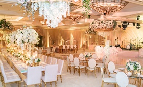 wedding reception ballroom flower print vinyl on long table flower chandelier gold chairs high low