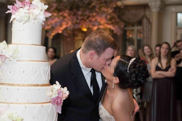 Bride and groom kiss beside a white and gold cake with white and pink flowers
