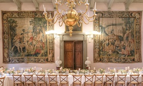 wedding reception long table wood vineyard chairs tapestry hanging on wall wood door villa venue