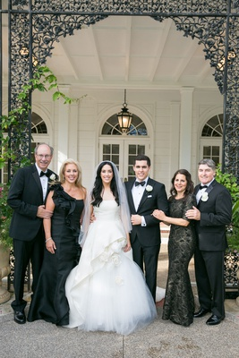 Wedding portrait bride and groom with parents mothers in black dresses one shoulder three quarter