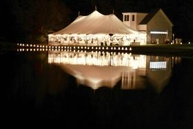 White tent wedding on lake illuminated with lights