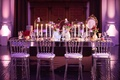 Rectangular wedding mirror table with clear chairs, red flower arrangements, and taper candles