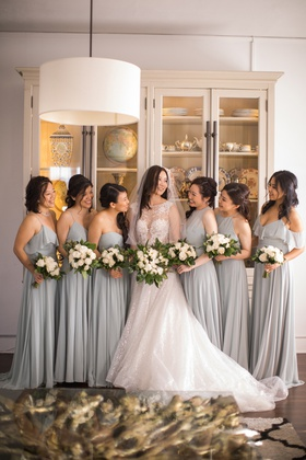 bridesmaids in pale grey-blue dresses with bride in berta a-line in the middle
