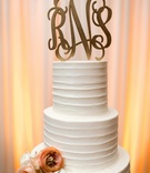 White textured wedding cake with orange flowers, gilded monogrammed topper