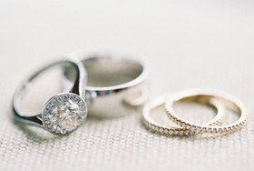 Bride's halo diamond engagement ring, groom's polished wedding band, and two pave yellow gold bands