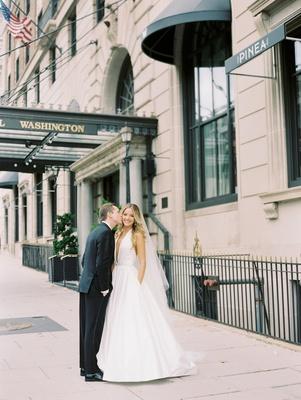 groom kissing bride's cheek, wedding dress with pockets, romona keveza wedding dress deep v