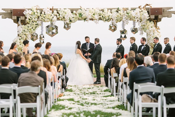 bride and groom stand at altar in oceanfront wedding ceremony with white floral details