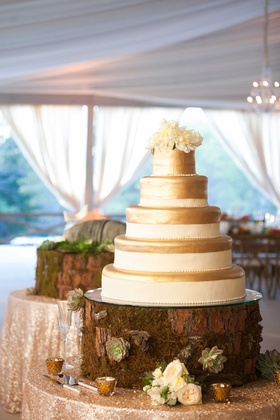 Tree stump with succulents and moss cake display with white and gold cake and fresh flower topper