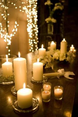 Ivory votive and pillar candles on wood table