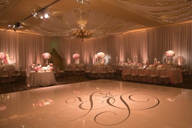 Silver wedding monogram on large white dance floor at wedding
