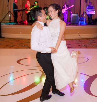 wedding reception gold monogram dance floor live band purple lighting first dance choreographed spin