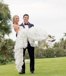 bride in marchesa wedding dress carried in the arms of her groom in tuxedo
