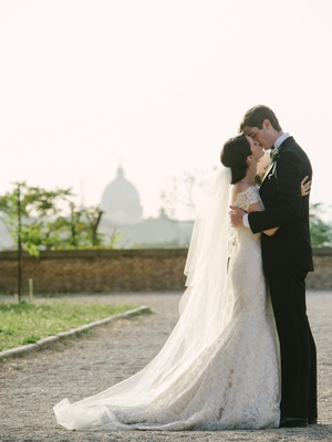 newlyweds kiss in rome with view of st peter's basilica