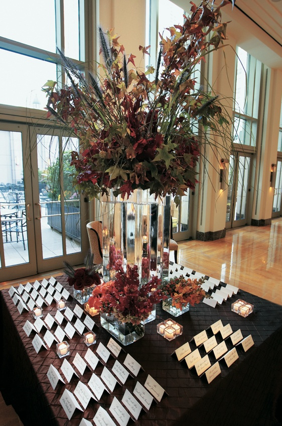 Seating cards and autumn leaves in vases
