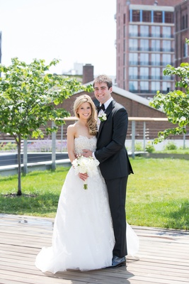 Bride in strapless reem acra wedding dress a line gown white bouquet blonde hair groom in tuxedo bow