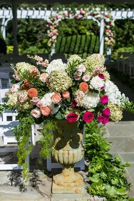 wedding ceremony decor stone urn with greenery pink orange white flowers rose hydrangea blooms