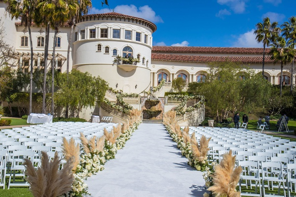 outdoor wedding ceremony monarch beach resort pampas grass lining aisle runner white chairs rotunda