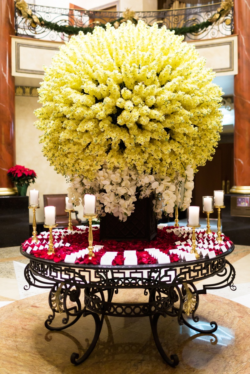 spherical display of ivory flowers and orchids, escort cards on bed of red rose petals