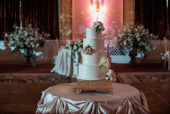 four-tiered wedding cake with fresh flowers and buttercream frosting