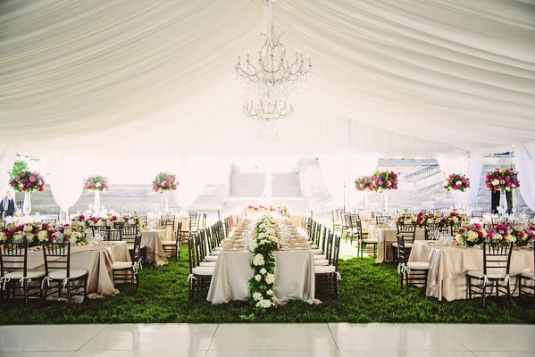 Tented wedding reception grass long rectangular tables flower runner and tall pink centerpieces