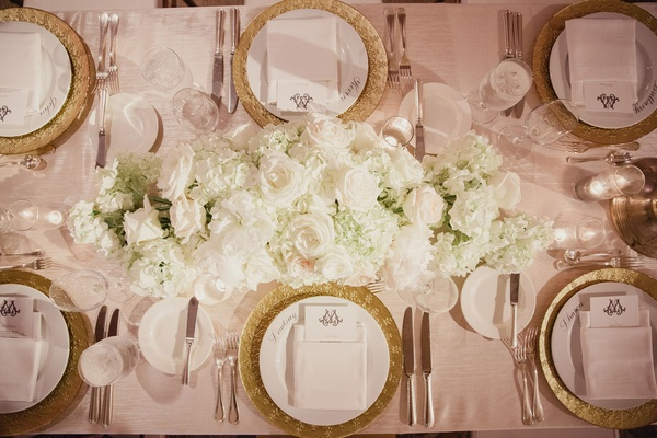 Gold charger plate and low centerpiece arrangement of hydrangea, roses, and peonies