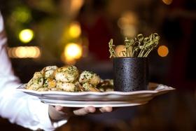 server holding platter of garlic herb shrimp on plate toothpicks wedding food ideas hors d'oeuvres