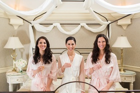 Bridal suite decorated with white sheets white bridal robe and pink bridesmaid robes champagne