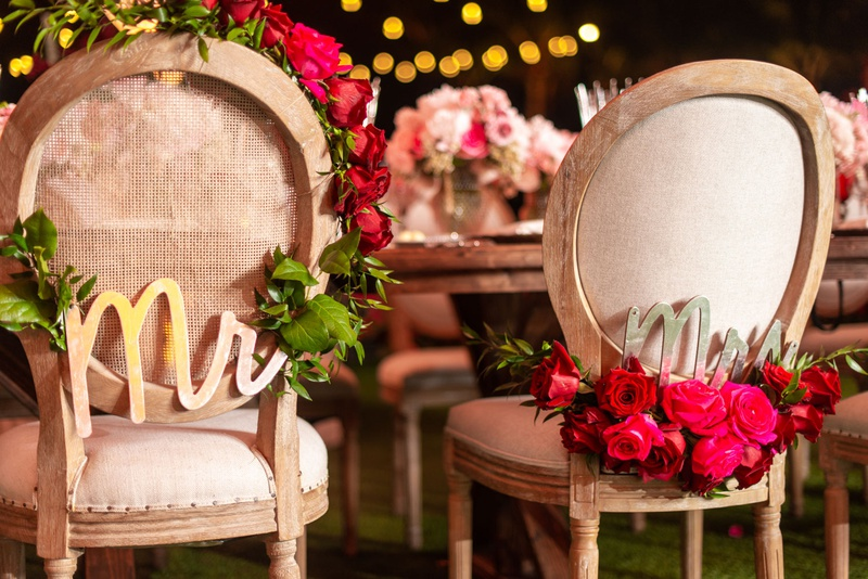 wedding reception wood round back chair with garland pink red rose flowers gold mr mrs signs