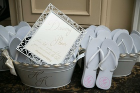 Wedding reception wedding favor flip flops with monogram in bucket with sign reading Dancing Shoes