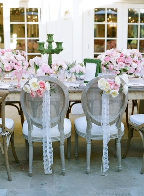 Lace vintage ribbon and white pink flowers on back of bride and groom reception chairs