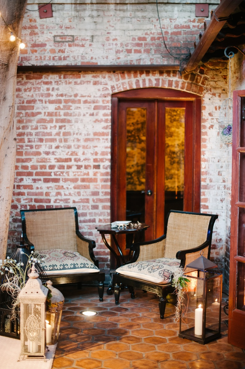 Armchairs on tile floor with brick walls and lantern decorations