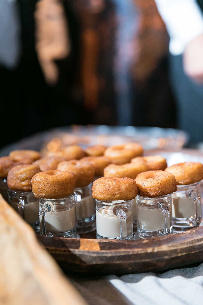 Miniature donuts apple cider on top of small glass mugs with milk creme cream dip